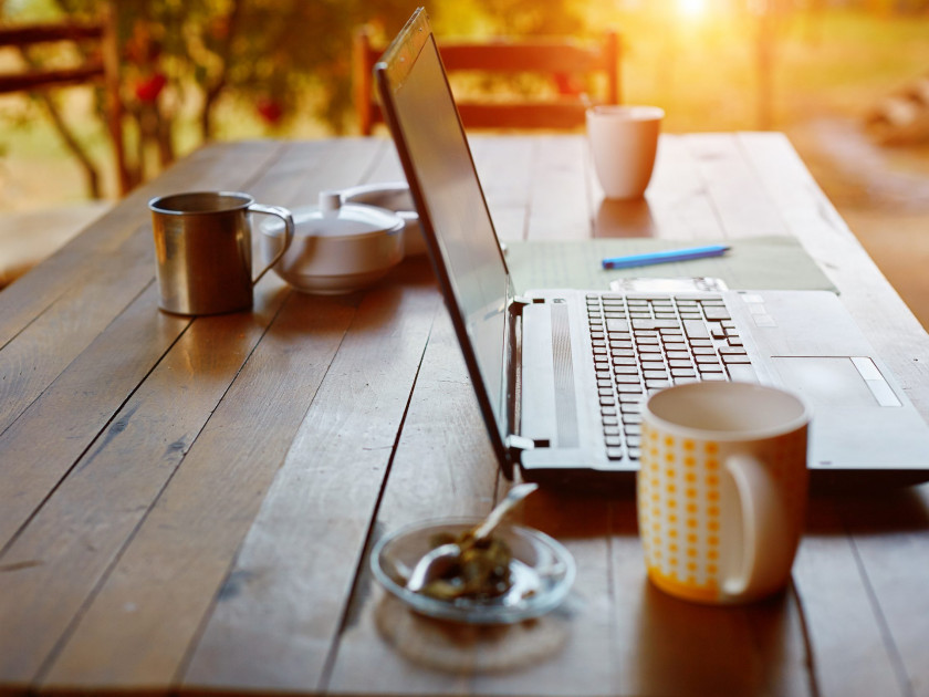 Laptop computer, phone and coffee in the garden - freelance or remote work concept. small depth of field, focus on the keyboard