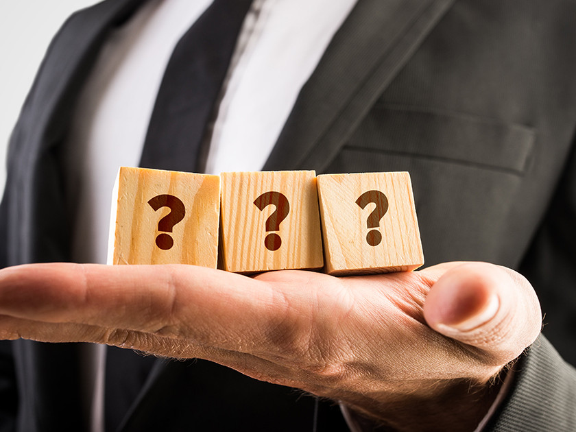 Businessman holding three wooden cubes displaying question marks.